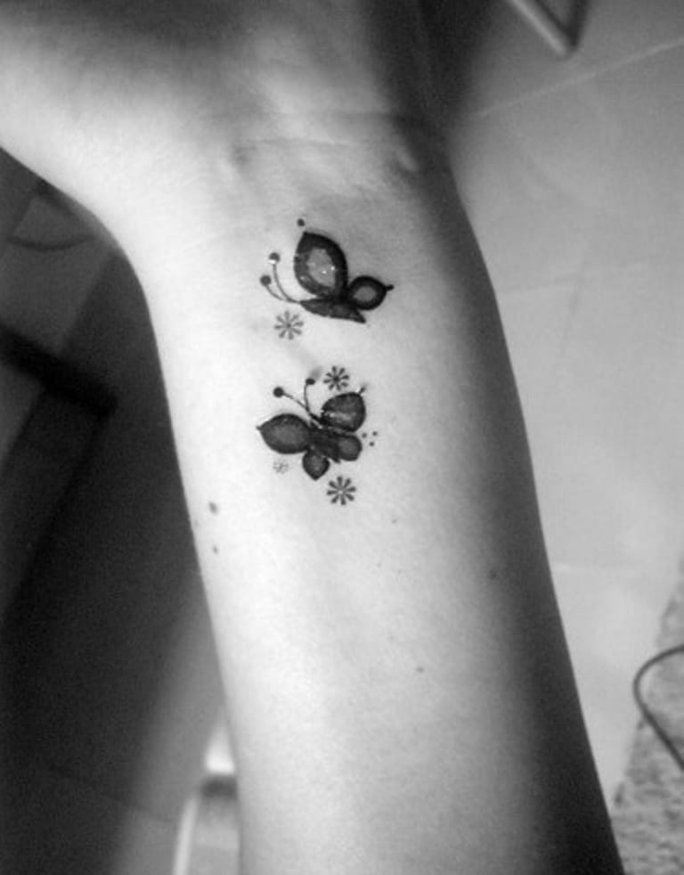 Tattoo of two small butterflies on wrist