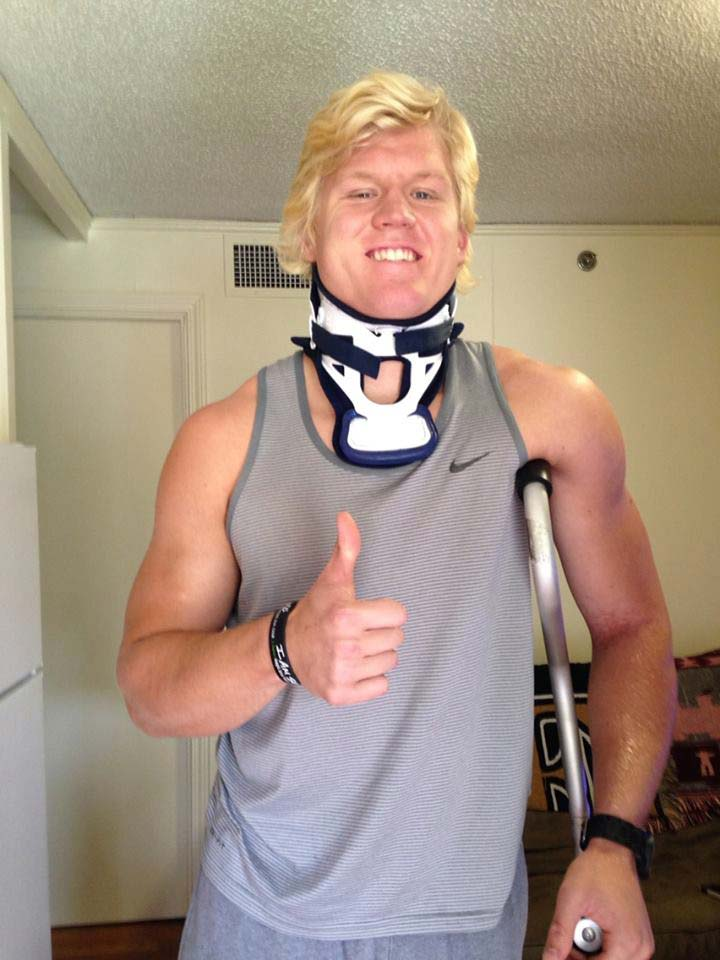 Zach with neck brace standing with one crouch under his left arm and right hand giving a thumbs up