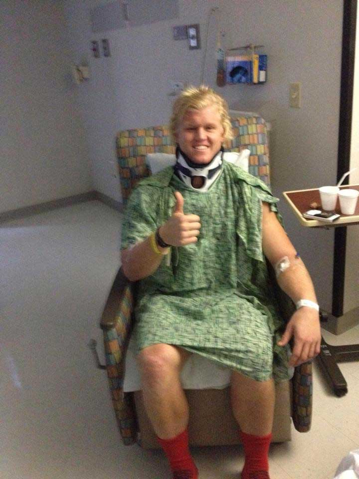 Zach Gordon in hospital chair with neck brace giving a thumbs up.