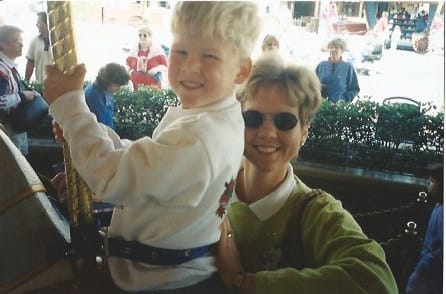 Zach as a little kid on merry-go-round with his mom