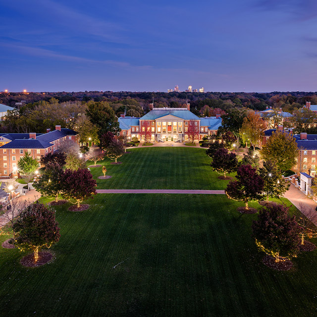 Reynolda Campus at night with Winston-Salem skyline in the background