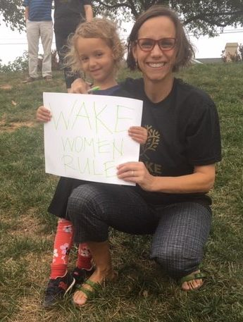 Parent smiling and crouching next to small child holding a sign at WFU Women's Soccer Game