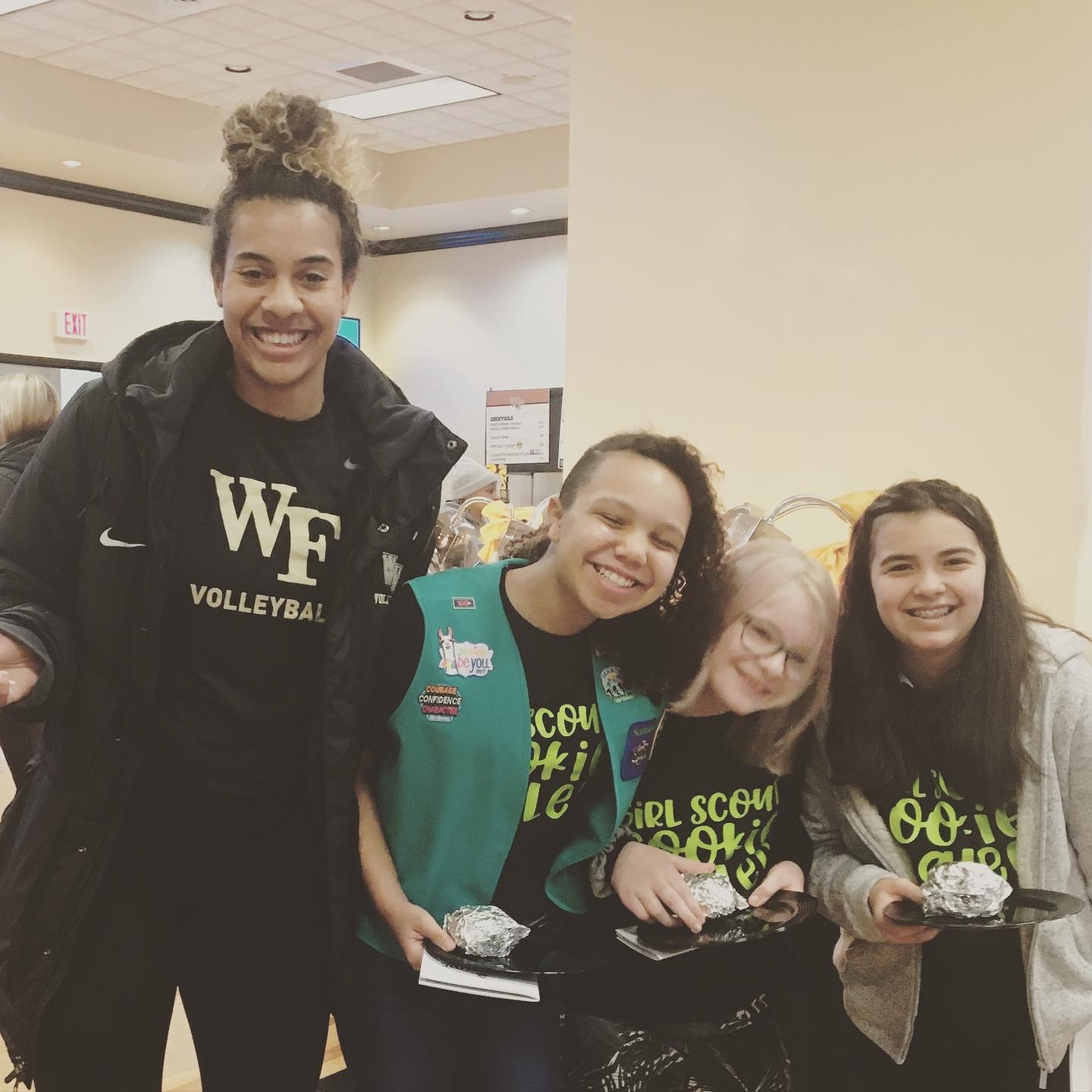 3 young girl scouts smiling with burritos accompanied by a Wake athlete