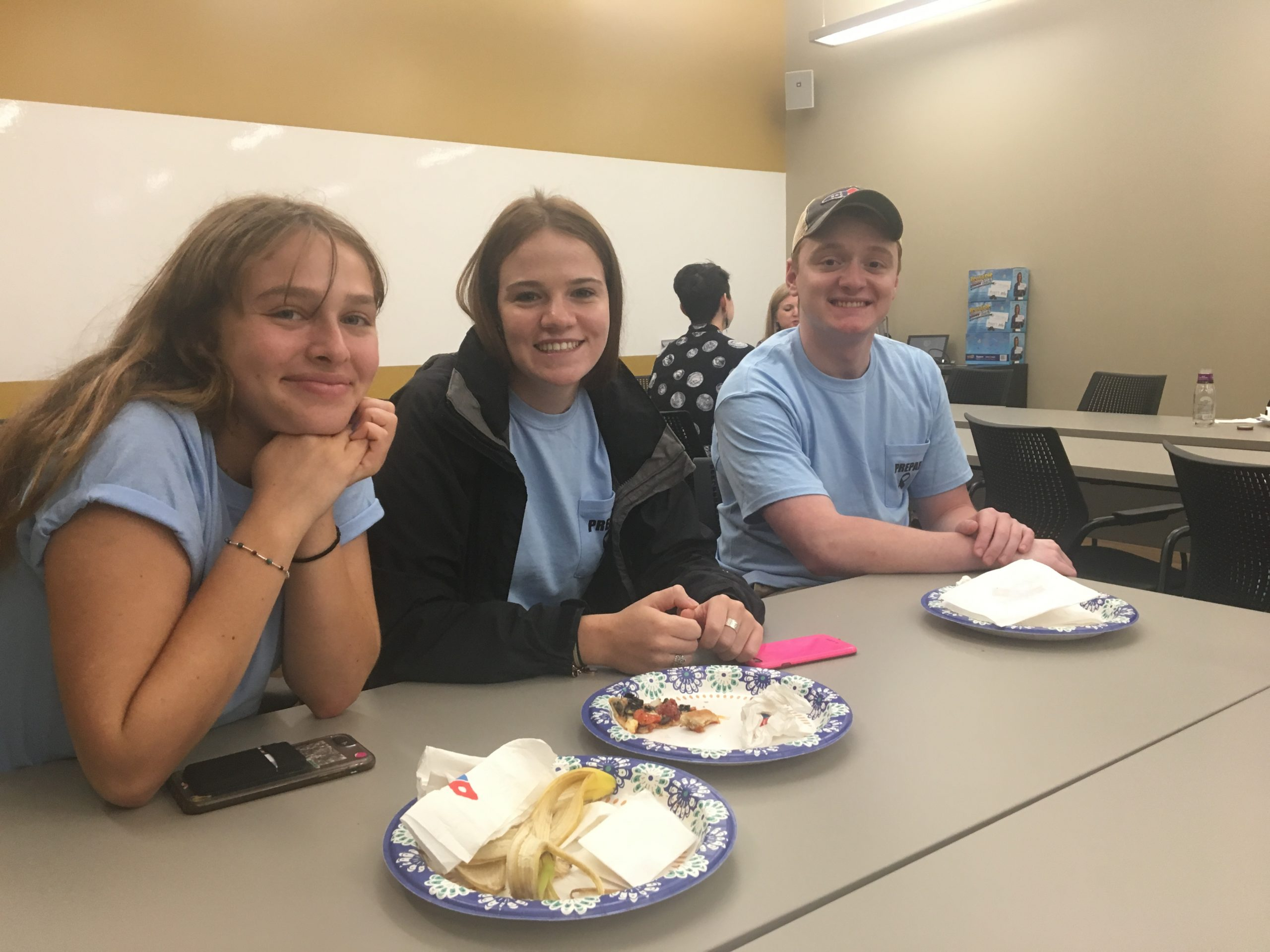 3 students smiling while sitting at a table