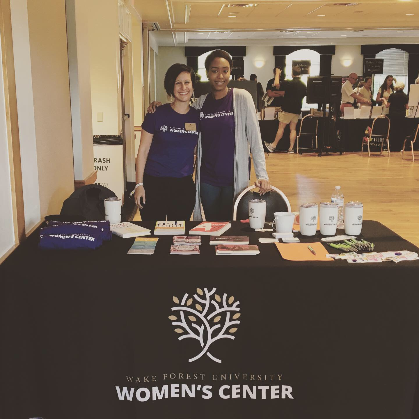 Director and student worker smiling while tabling at an event