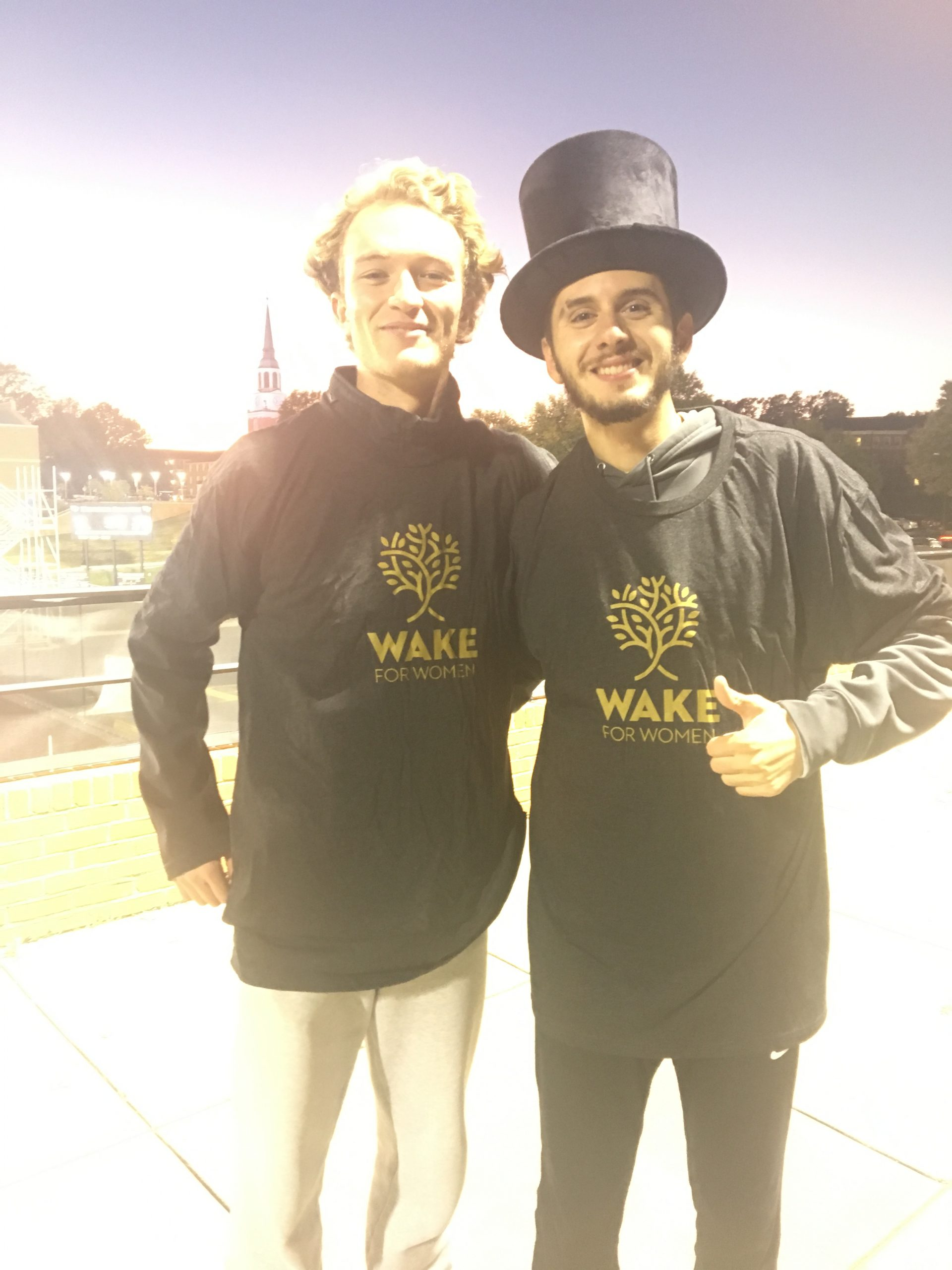 Two young male students in Wake for Women shirts.
