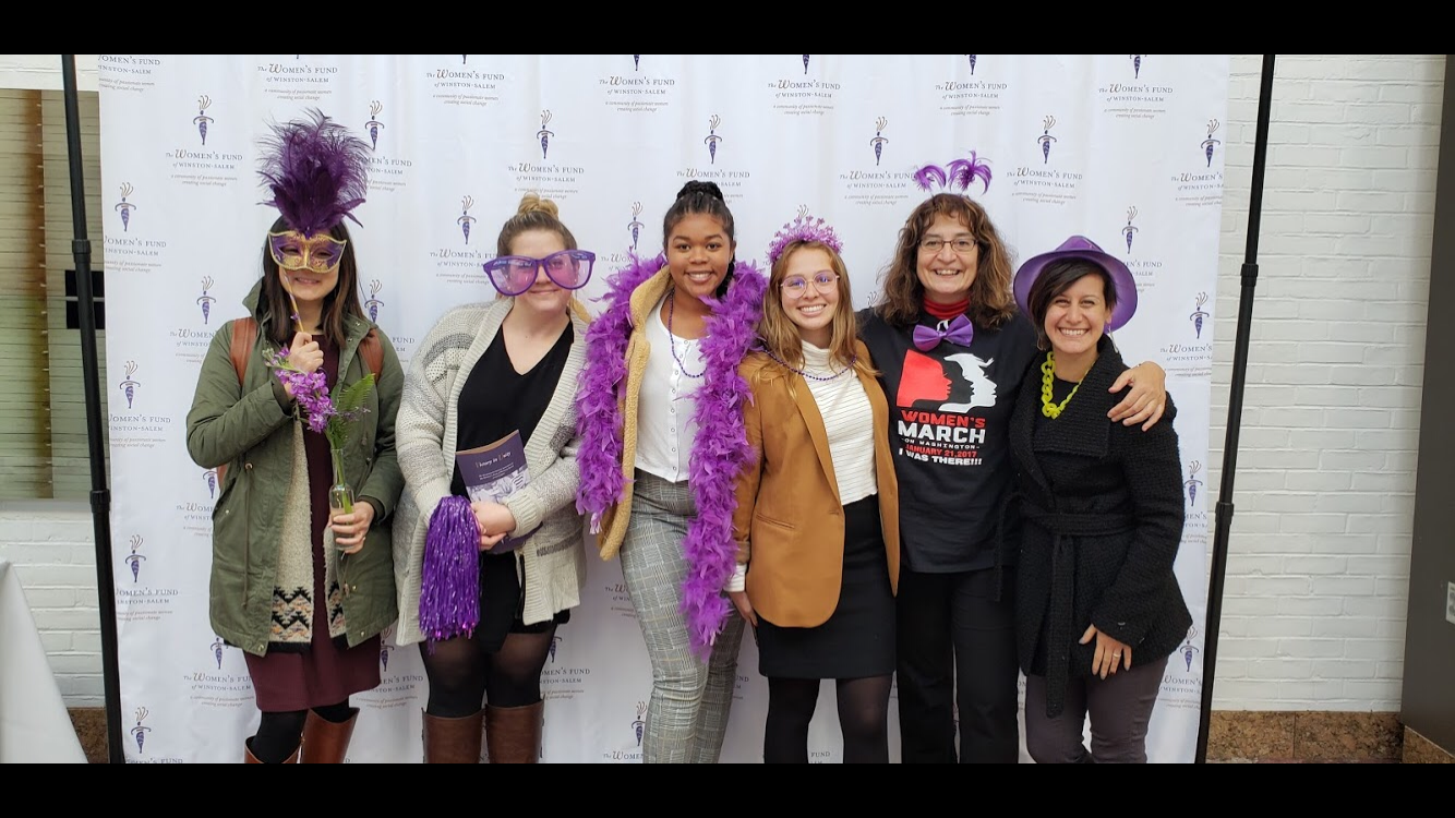 6 women from the women's center decorated in purple boas