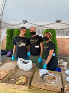 Women's Center staff serving pizza and refreshments to attendees.