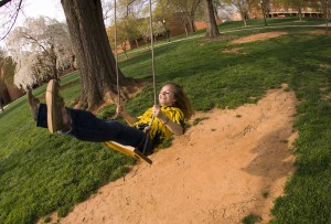 Wake Forest student plays on a swing on Davis Field.