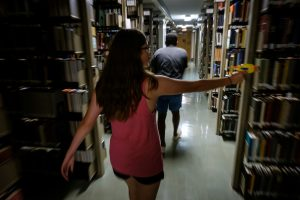 Students with NERF dart blasters search for zombies in the stacks of the ZSR Library