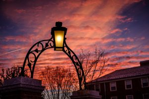 An ironwork arch on the Wake Forest campus frames clouds illuminated at dawn.