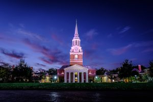 The bell tower of Wait Chapel rises above Hearn Plaza on the campus of Wake Forest University at dusk on Wednesday, October 18, 2017.