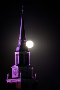 The full moon sets over the bell tower of Wait Chapel on the campus of Wake Forest University, Wednesday, October 24, 2018.