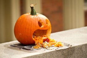 A carved pumpkin decorates the wall outside a residence hall, on the campus of Wake Forest University
