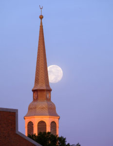 One day past full, the moon sets over the bell tower of Wait Chapel on the campus of Wake Forest University, Thursday, October 25, 2018.