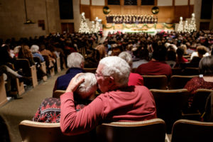 Wake Forest holds its annual Lovefeast ceremony in Wait Chapel on Sunday, December 8, 2019. The Lovefeast is a traditional Moravian service, and has been held at Wake Forest for more than 50 years. Here, an older man kisses the older woman beside him in a tender gesture..