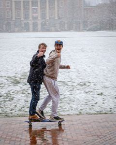 Students ride past the Chapel on a skateboard in the snow on Thursday, February 20, 2020.