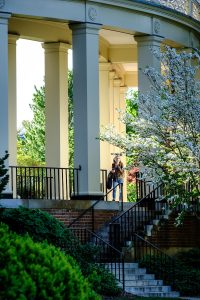 A Wake Forest student walks onto Hearn Plaza through the columns outside Efird Residence, on the campus of Wake Forest University, Friday, April 16, 2021.