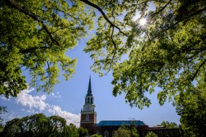 The bell tower of Wait Chapel is visible through large oak trees, on the campus of Wake Forest University, Wednesday, April 21, 2021.