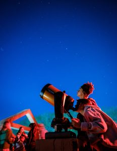 Wake Forest students learn to calculate the diameter of celestial objects using a telescope and basic trigonometry, in their astronomy class in Olin Hall on the evening of Thursday, March 28, 2019. Nathan Shepherd ('22) and Michelle MacDougald ('22) look through their telescope. The observation deck is bathed in red light to maintain the students' night vision.