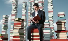 Man sitting on books and reading