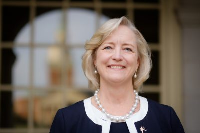 President Susan R. Wente in front of Reynolda Hall with Wait Chapel reflected.