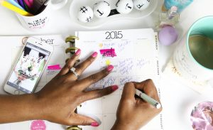 Woman's hand writing on a full paper calendar