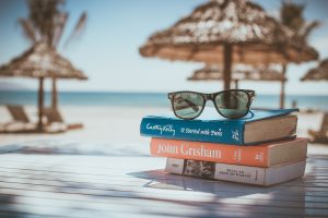 Photo of books and sunglasses sitting on a table with the beach in the background