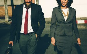 A man and woman walking down the street in business attire