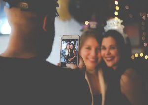 Man taking a picture on a phone of two women at a party