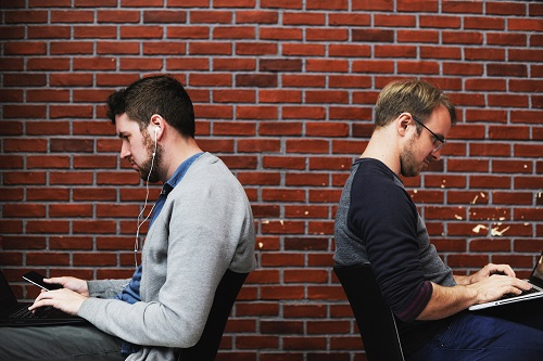 Two men working on laptops, sitting in chairs, with their backs to each other