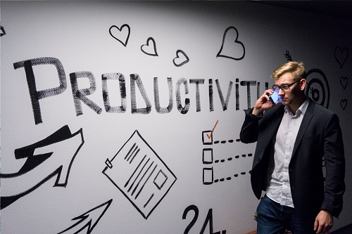 """Man walking in front of wall that says """"Productivity"""""""