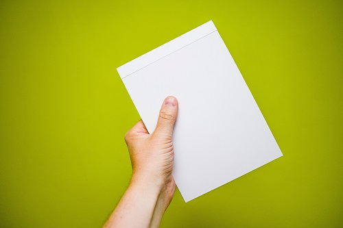 Person holding a sheet of paper in hand