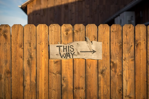 "Wood fence with a sign that says ""This way"" with an arrow pointing to the right"