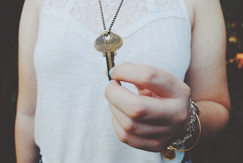 Woman holding a key on a chain around her neck
