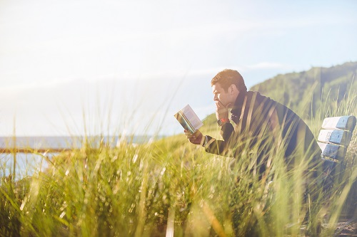 Man reading a book while sitting next to body of water