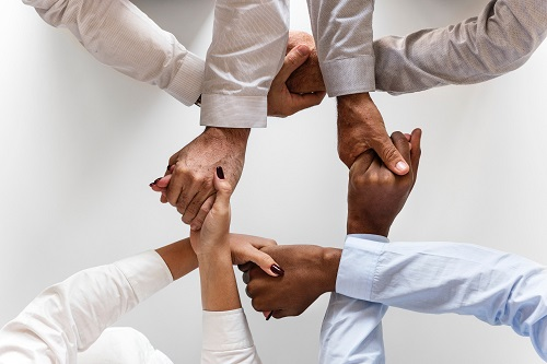 People holding hands and forming a knot