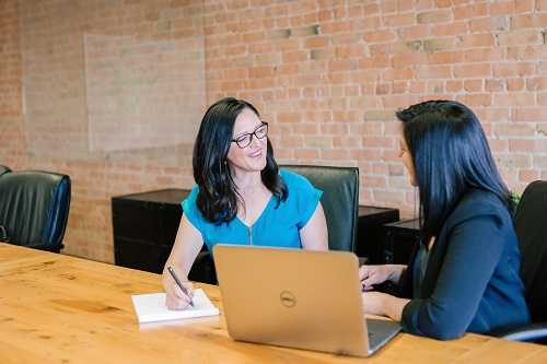 Two women talking at a conference room table