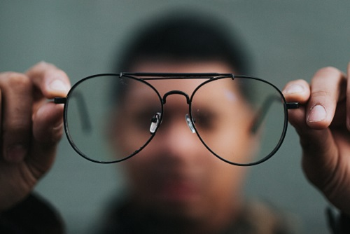 Man holding out glasses and looking through the lens.
