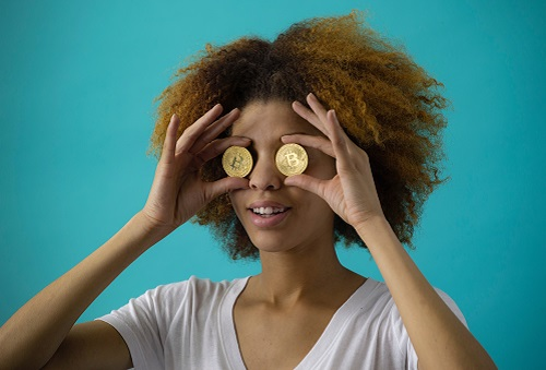 Woman holding gold coins over her eyes