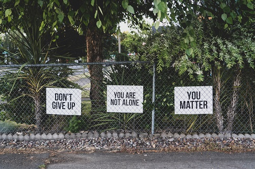 Gate with 3 signs posted that say Don't Give Up, You Are Not Alone, You Matter