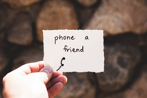 "Person holding up a piece of paper that says ""phone a friend"""