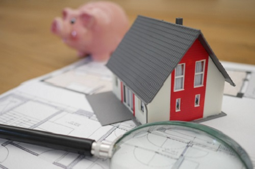 Piggy bank, model home, and magnifying glass sitting on a table