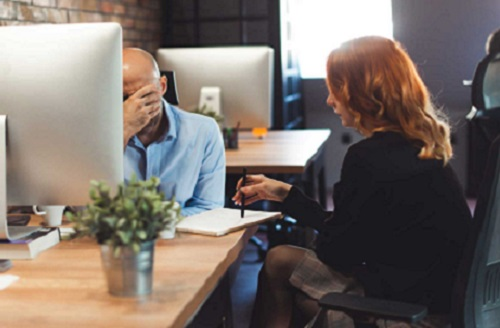 man and woman having a difficult conversation at work