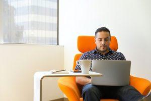 Man sitting on orange chair using laptop