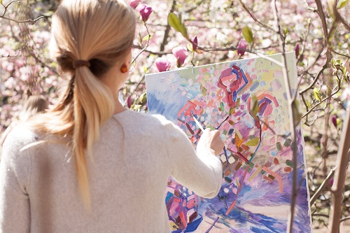 Woman painting outside on canvas