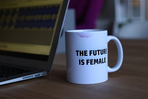 "Laptop next to a coffee mug that says ""the future is female"""