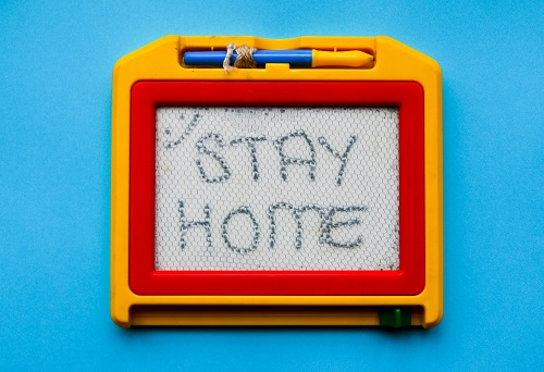 "Photo of etch-a-sketch with the words ""STAY HOME"""