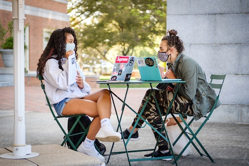 Two female students in masks sitting at a table together on campus