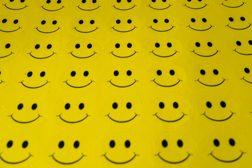 Smiley faces drawn on yellow paper
